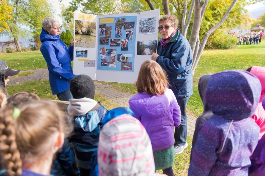 <who>Photo Credit: NowMedia</who> Lee McFadyen (right, facing camera) teaches young students about the river, the lake and the sockeye