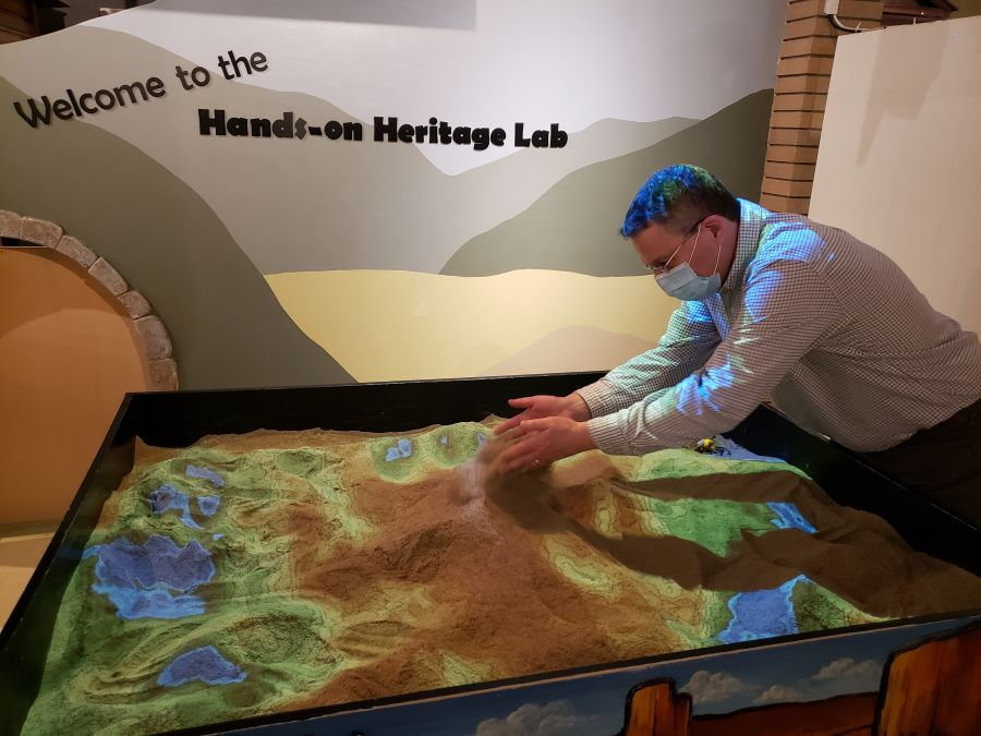 <who> Photo Credit: NowMedia </who> Penticton Museum Curator Dennis Oomen plays in the augmented reality sand box.