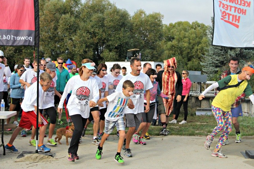 <who> Photo Credit: KelownaNow.com </who> Pork lovers getting ready to run during the 2014 Great Canadian Bacon Race.