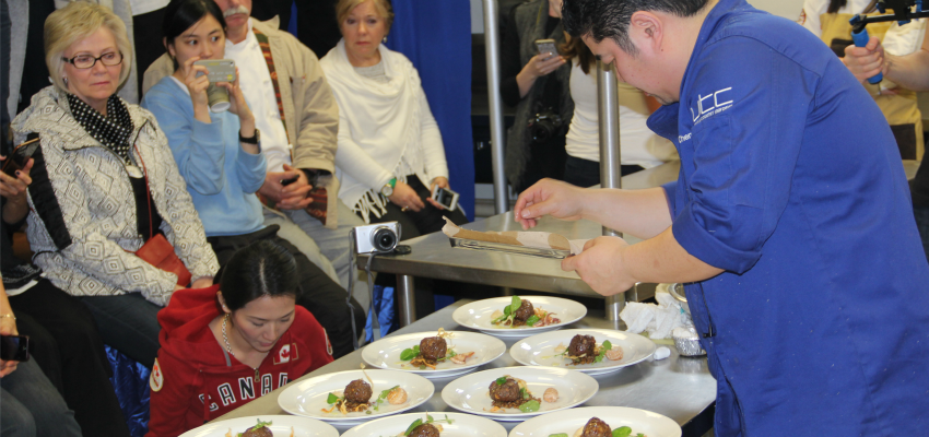 <who> Photo Credit: KelownaNow </who> B.C. Chef Alex Chen puts the finishing touches on his dish at the Black Box event.