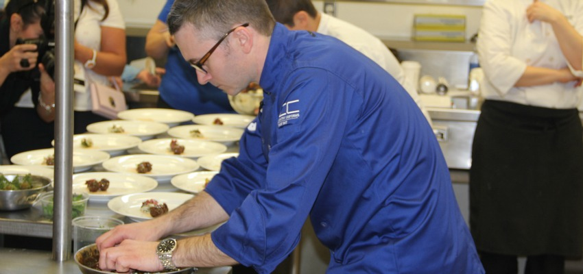<who> Photo Credit: KelownaNow </who> Ottawa Chef Marc Lepine finishes his dish for the Black Box Competition.