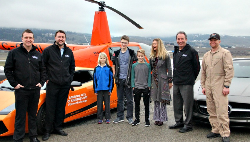 <who> Photo Credit: KelownaNow. </who> August Motorcar Representatives with the Donovan family at the Kelowna International Airport.
