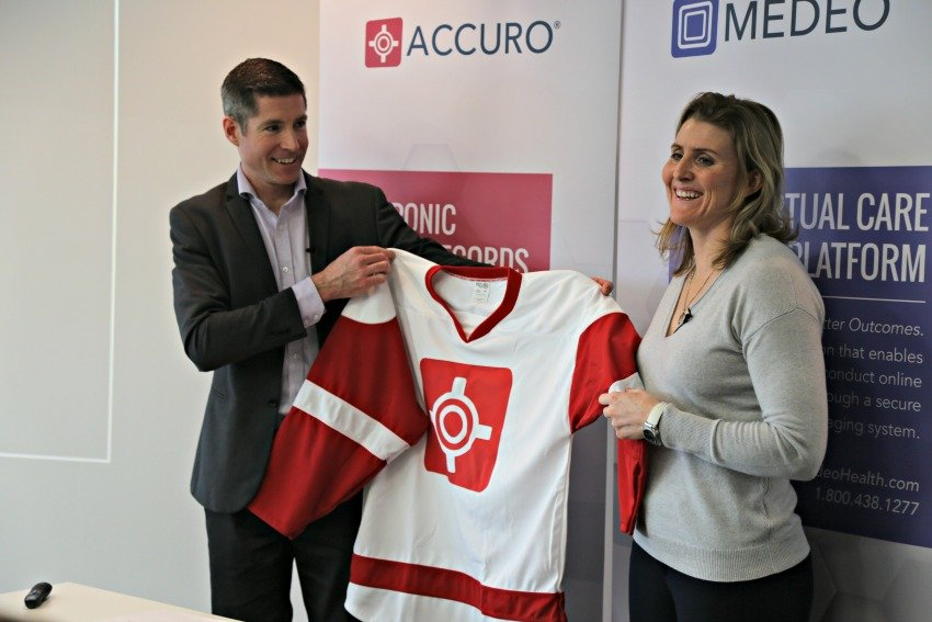<who> Photo Credit: KelownaNow.com </who> Mike Checkley presents Hayley Wickenheiser with a new QHR Technologies jersey.
