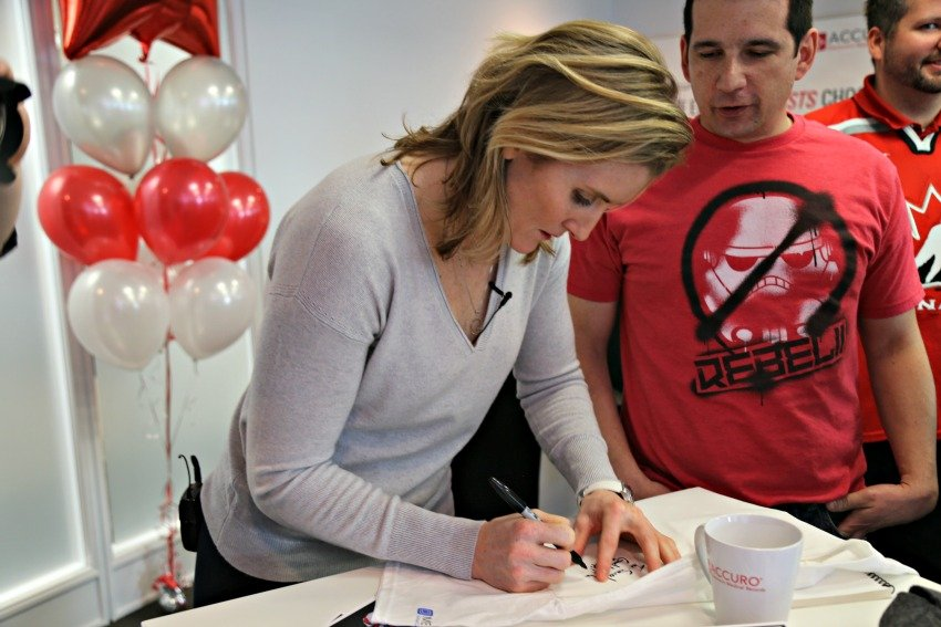 <who> Photo Credit: KelownaNow.com </who> Hayley Wickenheiser signs an autograph for a QHR Technologies staff member.