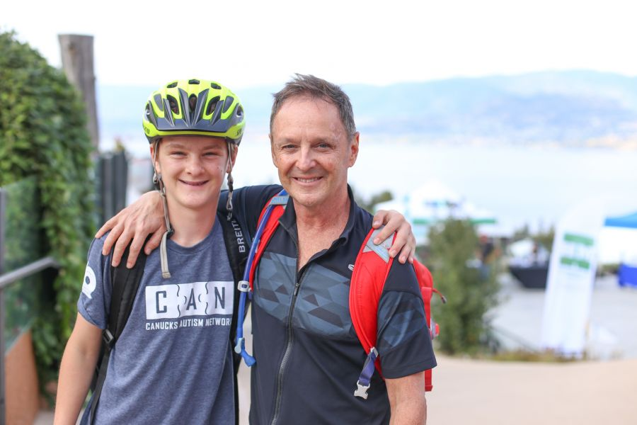 Two person side hugging each other and smiling. The younger boy is in a bike helmet and a CAN T-shirt. Marshall in red backpack.