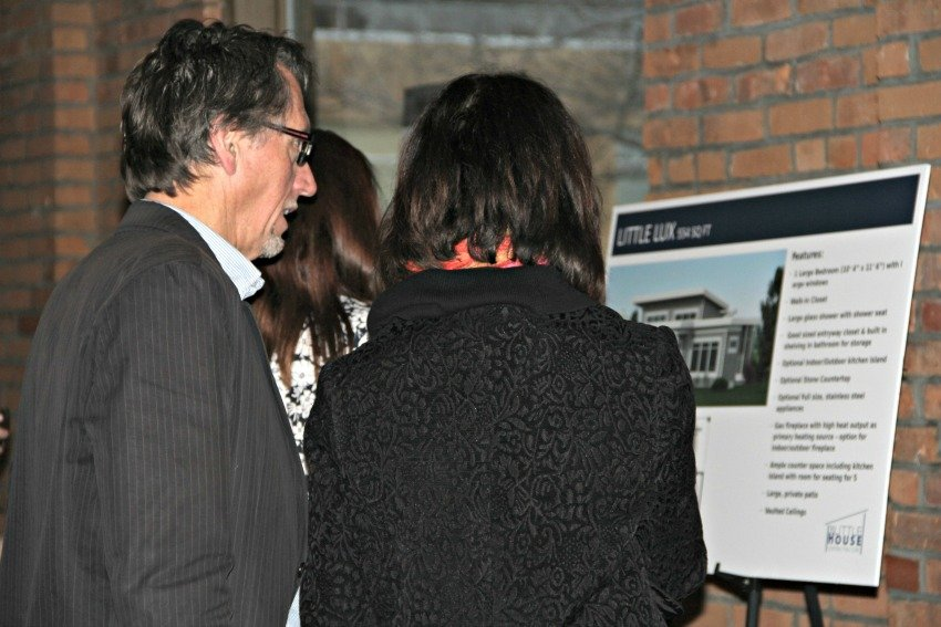 <who> Photo Credit: KelownaNow.com </who> Guests check out the micro home plans.