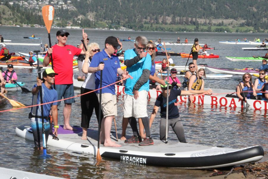 <who>Photo Credit: KelownaNow</who>Brad Dahl cutting the ceremonial ribbon to open the Kelowna Paddle Trail