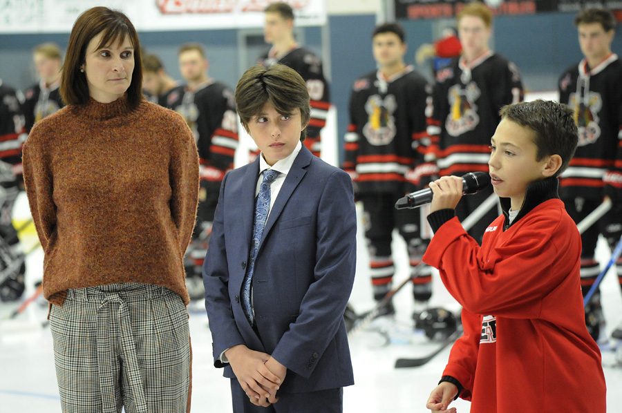<who>Photo Credit: Lorne White/KelownaNow </who>Twelve-year-old Scott Berg sings a stirring rendition of Hallelujah prior to Friday's game in honour of Grant Sheridan. Looking on are Sheridan's wife Cherie and son Tanner.