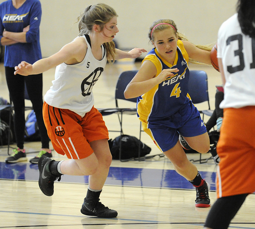<who>Photo Credit: Lorne White/KelownaNow </who>Kassidy Day of the UBCO U15 Junior Heat drives to the basket against Triple Threat.