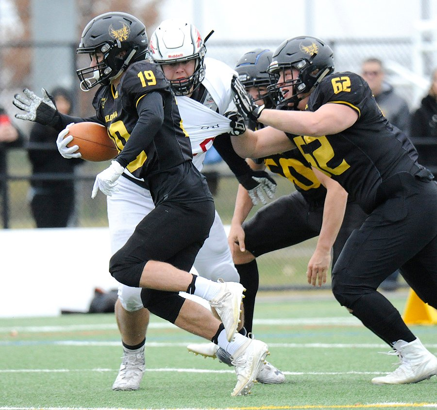 <who>Photo Credit: Lorne White/KelownaNow </who>Running back Noah Cross (19) will be relying on the Owls' offensive line, including Jack Marsland (52) to make room for what he does best.