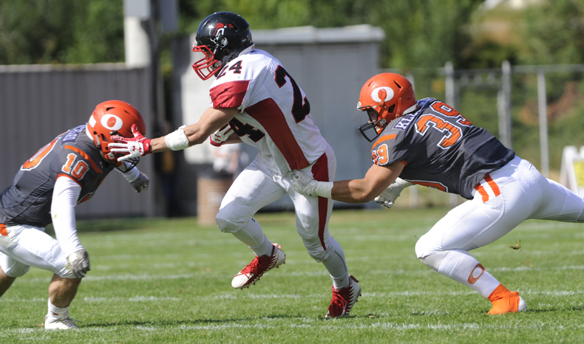 <who>Photo Credit: Lorne White/KelownaNow </who>Rhett Williams ran 17 times for 137 yards against the Sun defence that included Conor Richard, left, and Cole Klughart, right.