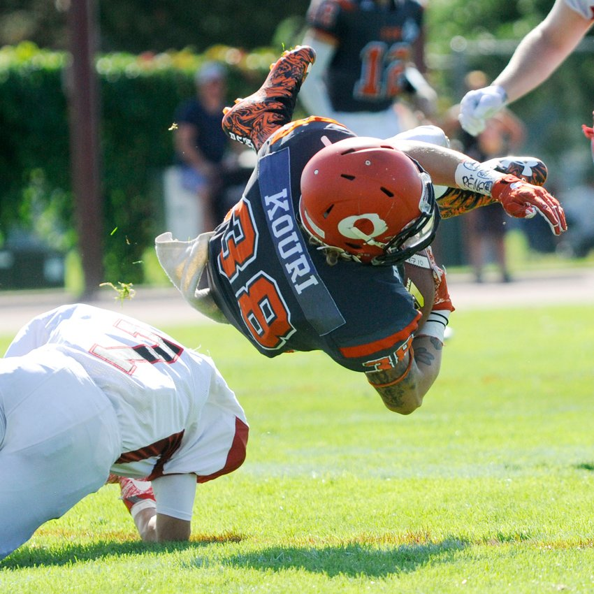 <who>Photo Credit: Lorne White/KelownaNow </who>Kelton Kouri of the Okanagan Sun is upended by Gevhahn McNally-Hardisty of the VI Raiders after a reception in the second quarter on Sunday at the Apple Bowl.