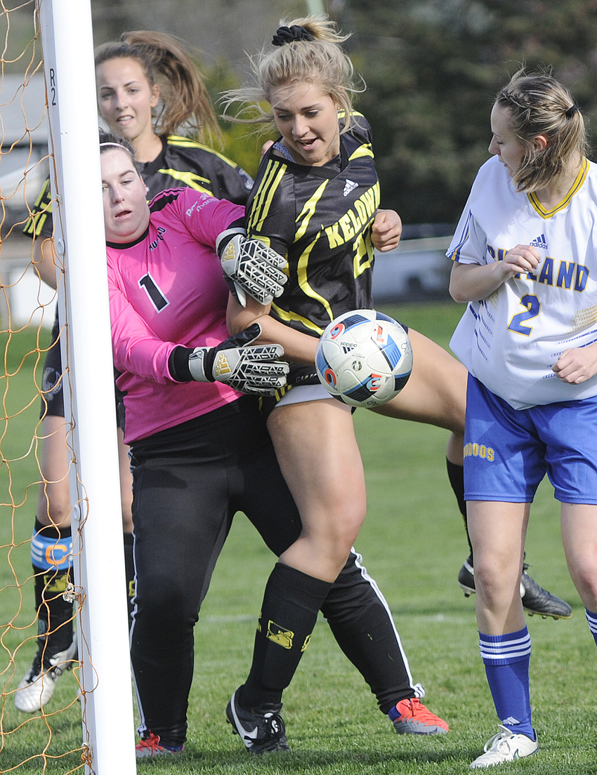 <who>Photo Credit: Lorne White/KelownaNow </who>Kate Armitage, left, of the Rutland Voodoos makes a save on deflection by the Kelowna Owls' Fiona Reha off a corner kick during their Okanagan Valley senior AAA soccer league match this week. To the right is Rutland's Courtney Blacklaws while Rene Watson of the Owls is in the background.