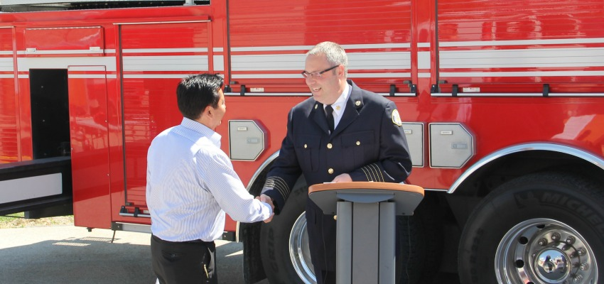 <who> Photo Credit: KelownaNow. </who> Louie shaking hands with fire Chief Jason Brolund.