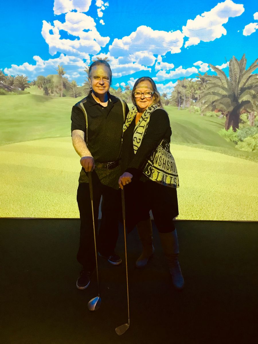 <who>Photo Credit: Contributed</who>Simplex Sportszone's Erwin and Rita Egert in front of one of their huge golf screens.
