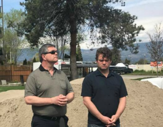 <who> Photo Credit: KelownaNow </who> Left: Shaun Reimer at media conference for flooding of the Central Okanagan.