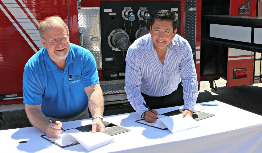 <who> Photo Credit: KelownaNow. </who> West Kelowna Mayor Doug Findlater and Westbank First Nation Chief Robert Louie signing the new agreement on Tuesday.